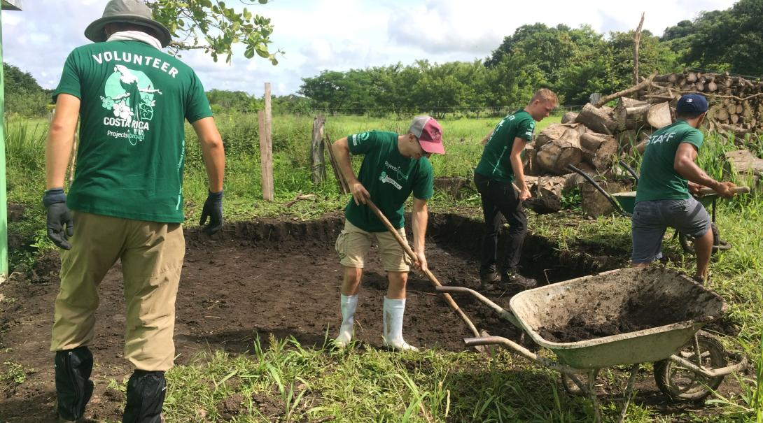 Volunteers working together as a team to help plant trees as part of a reforestation plan in Costa Rica